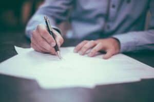 mand underskriver dokument